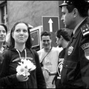 Activist holding flowers in front of police