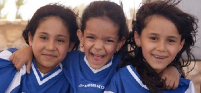 3 young girls playing soccer together